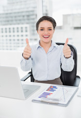 Businesswoman with graphs and laptop gesturing thumbs up in offi