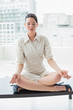 Elegant businesswoman in lotus position with eyes closed at offi
