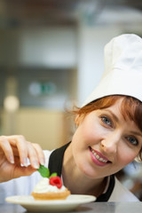 Smiling head chef putting mint leaf on little cake