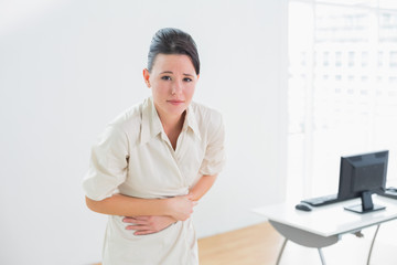 Businesswoman suffering from stomach pain in office