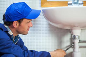 Attractive plumber repairing sink