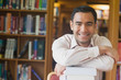 Cheerful attractive man posing leaning on a stack of books in li