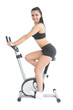 Slender fit woman training on an exercise bike smiling at camera