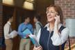 Amused mature student phoning standing in corridor