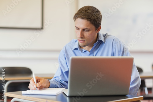 Concentrated male mature student using his notebook for learning