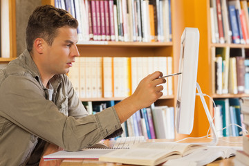 Handsome focused student pointing at computer