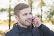 Close-up of a smiling man using cellphone outdoors