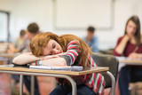 Blurred students in the classroom with one asleep girl
