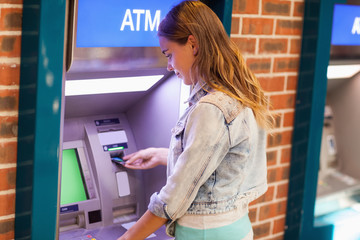 Pretty brunette student withdrawing cash