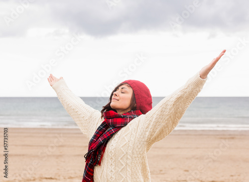 Woman in warm clothing stretching arms at beach