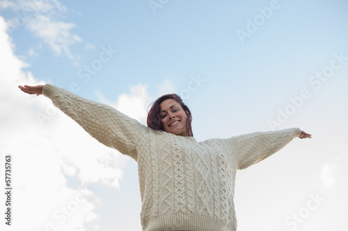 Woman in white sweater stretching her arms against sky