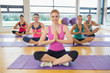 Class and instructor sitting in Namaste position on exercise mat