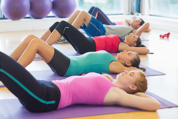 Class lying on exercise mats in row at fitness studio