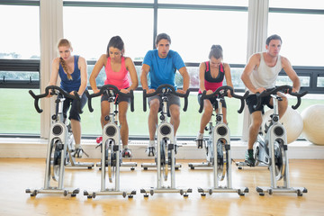 Determined people working out at spinning class in gym