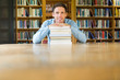 Smiling mature student with stack of books at library desk