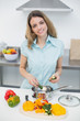Lovely smiling woman cooking standing in kitchen