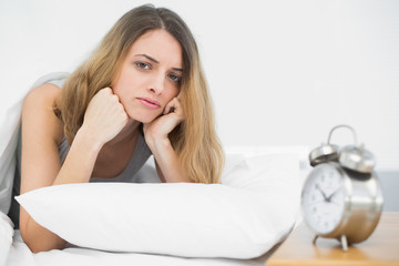 Serious brunette woman lying on her bed under the cover