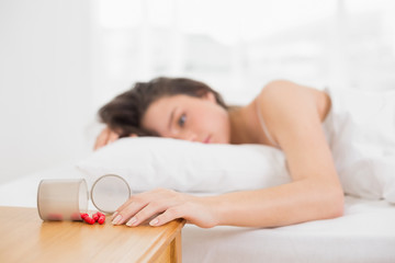 Woman in bed by spilt bottle of pills on table