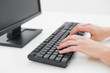 Hands typing on keyboard in an office