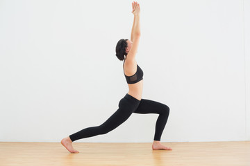 Sporty woman doing the warrior pose in fitness studio