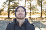 Smiling man in warm clothing looking up in forest