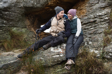 Smiling couple sitting on rock while on a hike