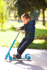 Boy riding a scooter in park