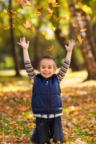 Joyful kid playing with leaves
