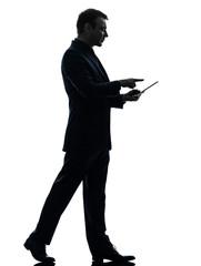 business man walking touchscreen digital tablet  silhouette