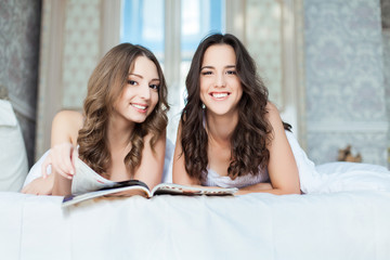 Two Beautiful Women with magazine in the Bedroom