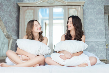 Two Beautiful Women with pillow laughing together on the bed