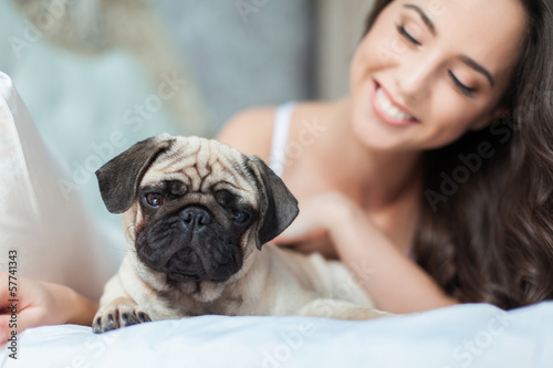 Attractive young girl with dog while laying on bed