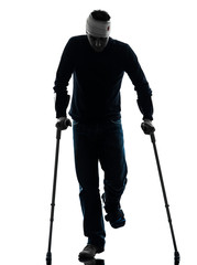 injured man walking with crutches silhouette
