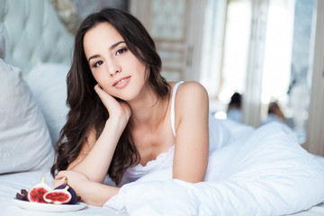 Attractive woman with a figs on the bed