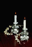 two lighted candles in elegantnyh candlesticks