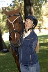 Female rider hugging horse smiling happy