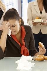 Unhappy office worker eating doughnut