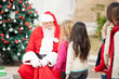 Santa Claus Looking At Children Standing In A Queue