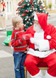 Boy Giving Wish List To Santa Claus