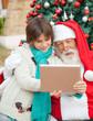 Santa Claus Using Digital Tablet With Boy