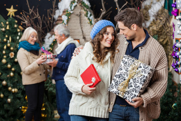 Couple Holding Christmas Presents With Parents In Background