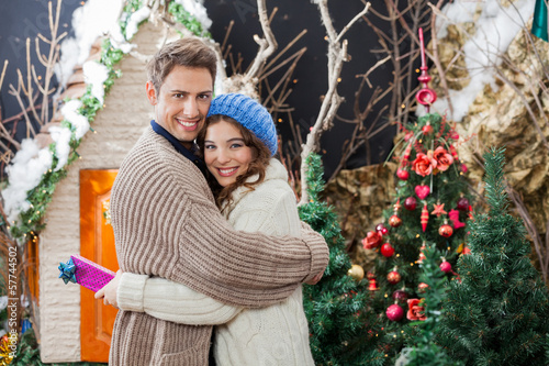 Portrait Of Couple With Gift Box Embracing At Christmas Store