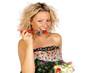 Frau mit Salat in der Hand ißt eine Tomate