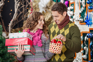 Happy Young Couple With Presents In Christmas Store