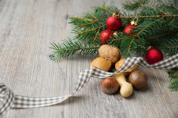 Tannenzweig mit Christbaumugeln und verschiedenen Nüssen