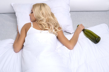 Sleeping drunk girl with empty bottle.