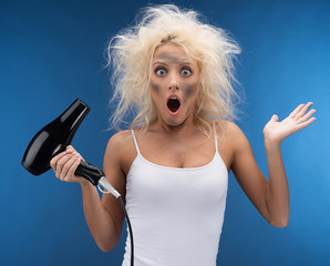 Funny blond girl having problem with hairdryer.