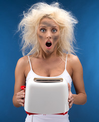 Funny blond girl having trouble with toaster.