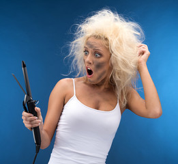 Funny blond girl curling hair with broken device.