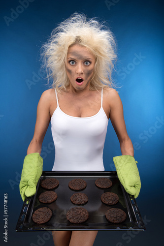 Burnt cookies. Funny blond girl have trouble with cooking
